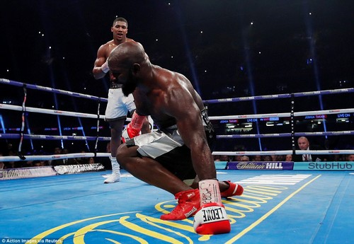 Joshua knocks Takam down to one knee in the fourth round after opening a huge cut above his opponent's right eye
