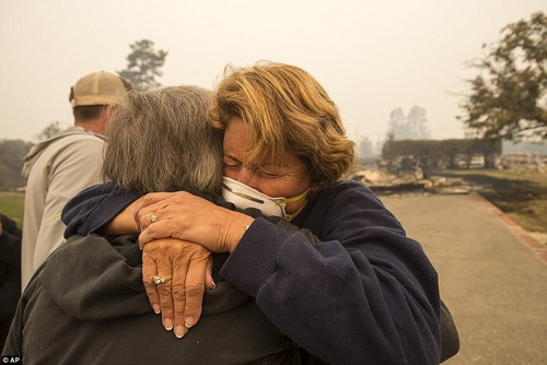 Northern California'a deadly wildfires have killed 15 and injured at least 100 (Pictured, Kim Graves, left, hugs her neighbor Susan Gaynard on Tuesday after they both lost homes during a wildfire in Sonoma County)