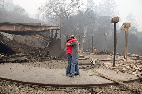 At least 183 people are missing and more than more than 2,000 homes and businesses have been destroyed (Pictured,Rhonda Readen, left, hugs her crying partner, Tim Shirley after they arrived on Tuesday to find their residence in the Fountaingrove area of Santa Rosa)