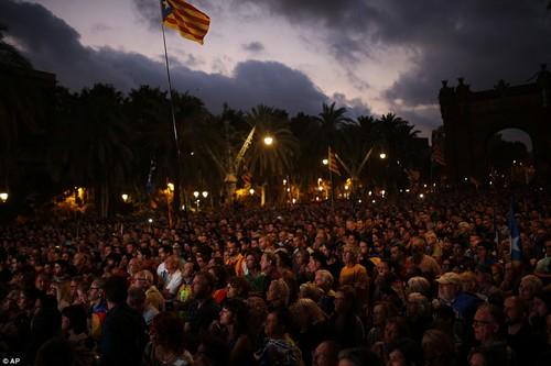 Pro-independence supporters during a rally as they watch Catalan President Carles Puigdemont speaking in parliament on a giant screen in Barcelona