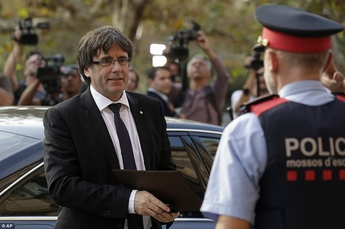 Catalan regional President Carles Puigdemont arrived at the parliament in Barcelona earlier today and greeted a policeman