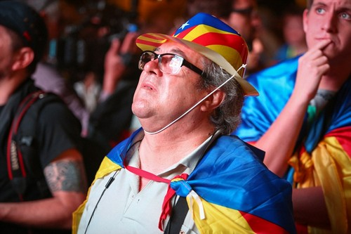 A hopeful Catalan looks up at the big screen in Barcelona while wearing a hat and cape featuring the Catalan flag