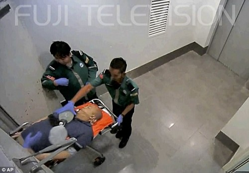 A paramedic pumps air into the victim's mouth through a tube as Kim Jong-nam is seen passed out on the stretcher