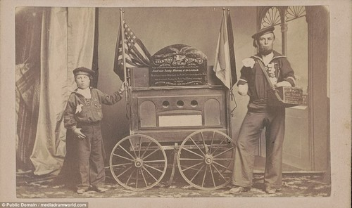 Bernard Tobey (right) poses with his son (left). Tobey became a double amputee during the war. He is pictured standing beside aa small wagon displaying Secretary of War Edwin Stanton's dispatch on the fall of Fort Fisher shortly after the conflict