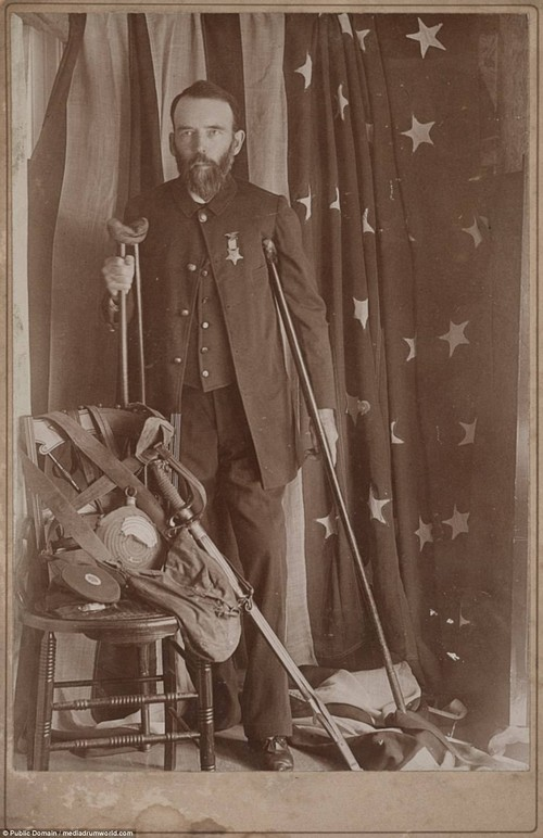 It is not clear what this soldier's name is, although he is presumably a Unionist soldier as he poses by the American flag. He is forced to use a crutch after his right leg was wounded in the conflict