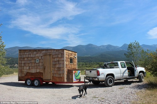 The couple's homemade home is parked up on some gravel and attached to their Nissan Frontier pick-up which has two bicycles in the back and the back driver's side window is decorated with graffiti depicting the sun and the word 'smile'