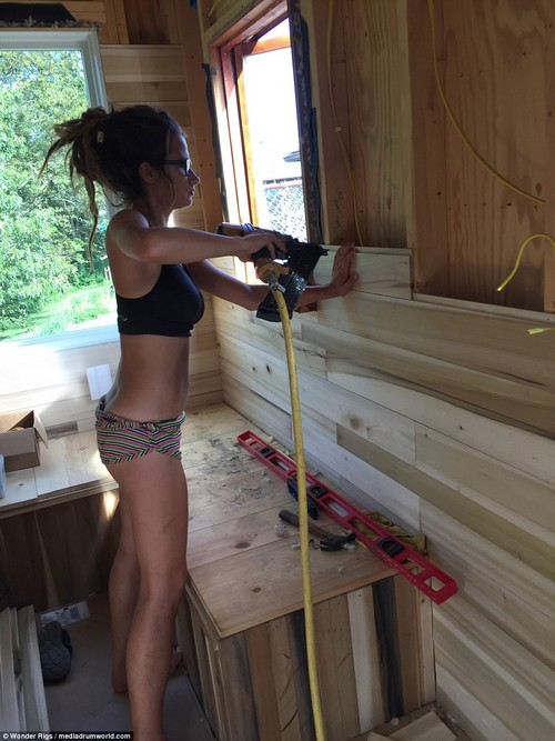 Margarita, pictured before cutting off her hair, uses a power tool to construct the inner walls of the living area of their tiny, mobile home. On the bench in front of her is a spirit level to make sure the slats are straight