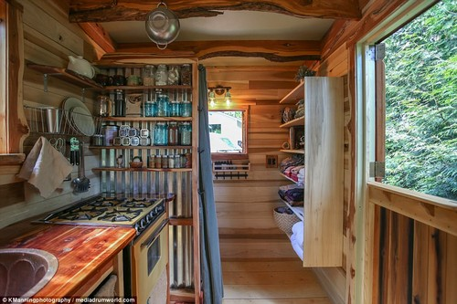 The kitchen, which is fitted with a four-hob gas oven, is seen with shelves for storing utensils, ingredients and crockery as well as a large window giving it plenty of natural light