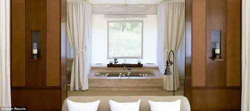 The light-filled bathing area features a free-standing bathtub and shower, while the living room has twin writing desks