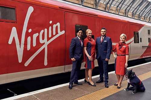 New route: Virgin Trains staff show off the new tailored uniforms designed by Wayne and Gerardine Hemingway, which are billed as 'body-neutral'