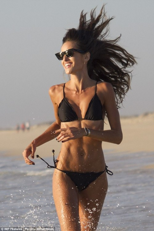Looking good:The Victoria¿s Secret Angel showed off her lithe body in a striking black bikini while frolicking on the sand in Comporta