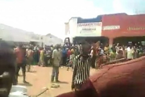 In video of the woman's execution, the leader of the rebel group, Kalamba Kambangoma, is seen grabbing the woman by the hair before she is taken to the stage to be publicly raped while a crowd of people (pictured above) watched