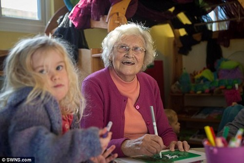 The grandmother joins in with drawing, singing and dancing with the class of 2-4 year olds