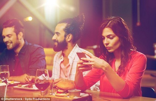 Worrying new research has revealed we reach for our smartphones around 4,000 times a year for no apparent reason (stock image)