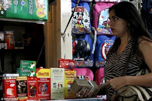 A woman holds a stack of bolivar notes in a stall selling medicines at a market in Rubio. Just one bottle of antibiotics costs double the minimum wage