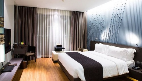 Шоколадные атласные шторы в интерьере спальни.