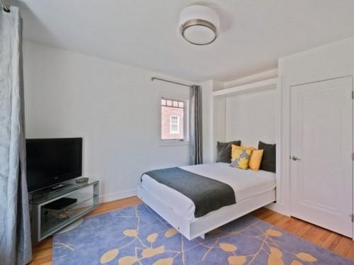 Расположить шкаф со встроенной кроватью можно вдоль узкой стены и, оставив достаточное место для опущенного спального места, расставить в комнате остальную мебель.