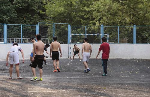 In the winter, many courtyard football pitches are turned into ice rinks. But now, with temperatures nearing 30 degrees Celsius, players are looking to stay cool.