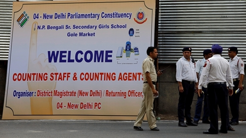 A policeman walks past a hoarding outside a vote counting centre in New Delhi