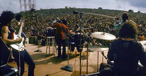 Carlos Santana (left) and his band perform on stage to a huge audience at the original Woodstock festival.