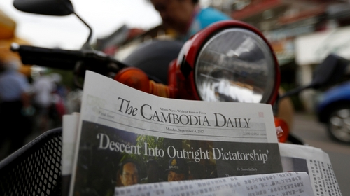 A woman buys the final issue of The Cambodia Daily newspaper at a store along a street in Phnom Penh