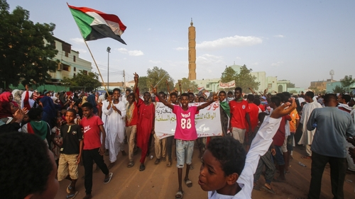 Sudanese people chant slogans and wave national flags as they celebrate in Khartoum