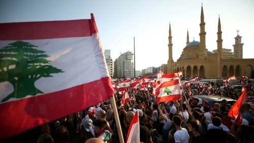 Demonstrators carry national flags during an anti-government protest near Al-Amin mosque in downtown Beirut, Lebanon October 20, 2019.