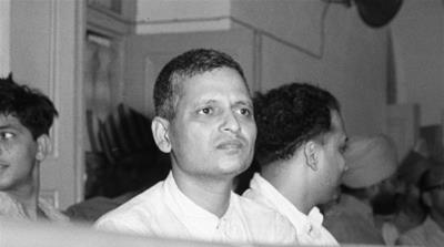 Nathuram Godse, left, one of nine co-defendants in the Mohandas Gandhi assassination conspiracy case, and defense counsellor L.B. Bhopatkar confer May 27, 1948, at the start of the hearing. (AP Photo)