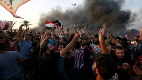 Demonstrators shout slogans as they block the road with burning tires during a protest over unemployment, corruption and poor public services, in Baghdad