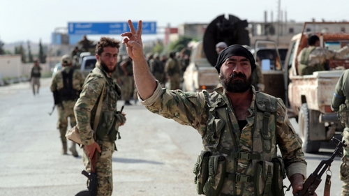 A Turkey-backed Syrian rebel fighter gestures to the camera at the border town of Tel Abyad, Syria, October 14, 2019