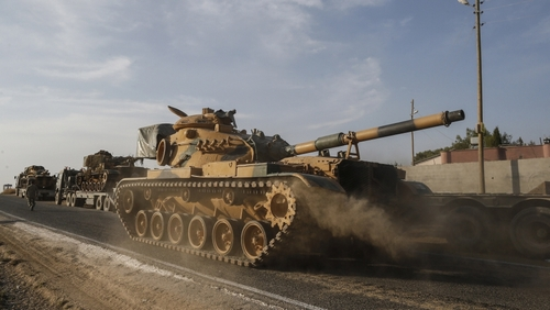 A Turkish forces tank is driven to its new position after was transported by trucks, on a road towards the border with Syria in Sanliurfa province, Turkey, on Monday, Oct. 14, 2019