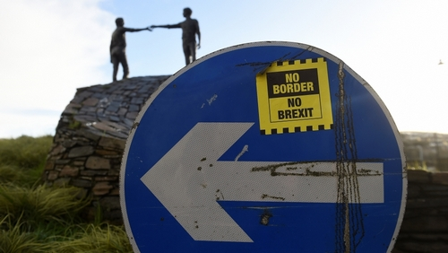 A ' No Border, No Brexit' sticker is seen on a road sign in front of the Peace statue entitled 'Hands Across the Divide' in Londonderry, Northern Ireland, January 22, 2019